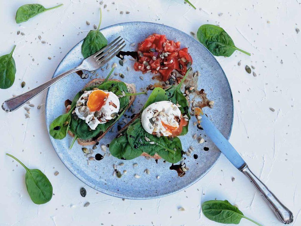 Leckeres Frühstück: Pochierter Eier mit Spinat und Tomatensalat